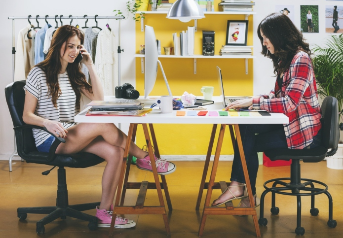 Two female fashion bloggers sitting at