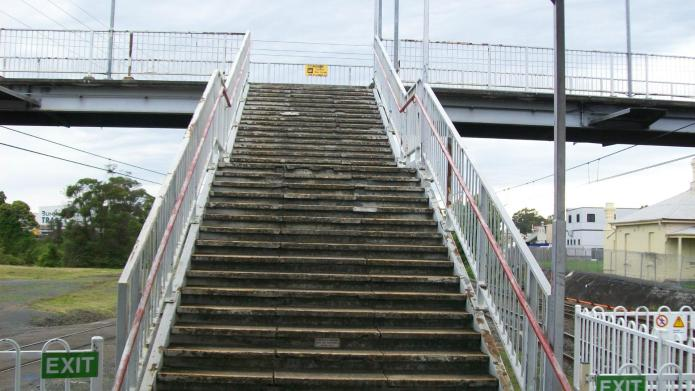 Amputee struggles up the stairs at