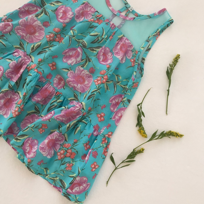 Floral tank top with leaves next to it