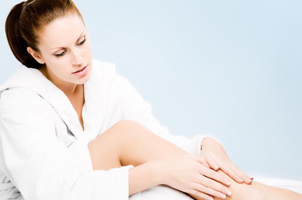 Woman moisturizing legs with lotion