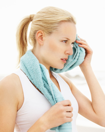 Woman wiping sweat from her forehead after workout