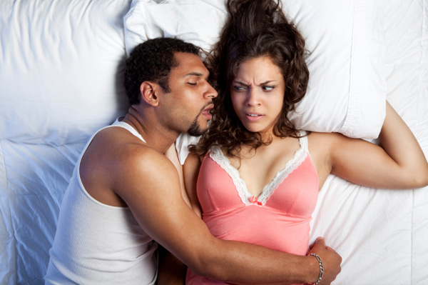 Annoyed woman in bed with husband