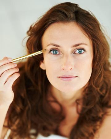 Woman applying eye makeup