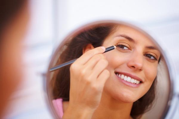 Woman applying eye liner