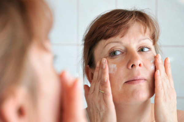 Woman applying lotion to aging skin
