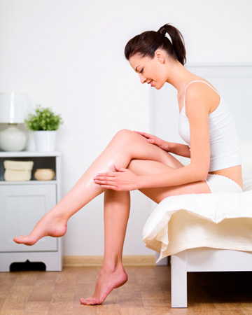 Woman applying lotion to legs