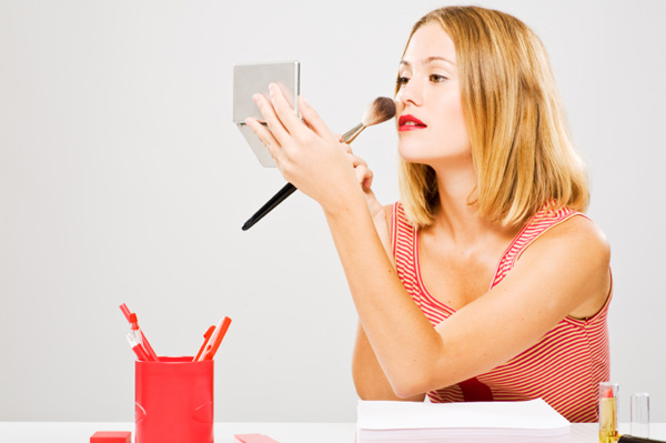 Woman applying makeup in office
