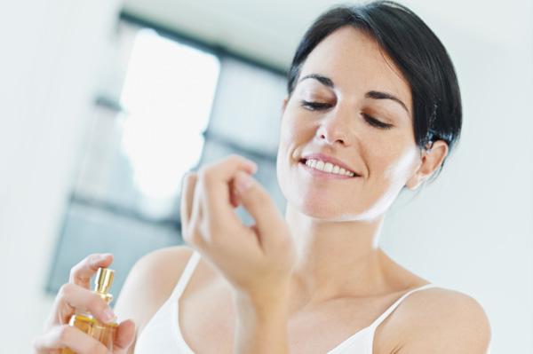 Woman applying perfume to wrist