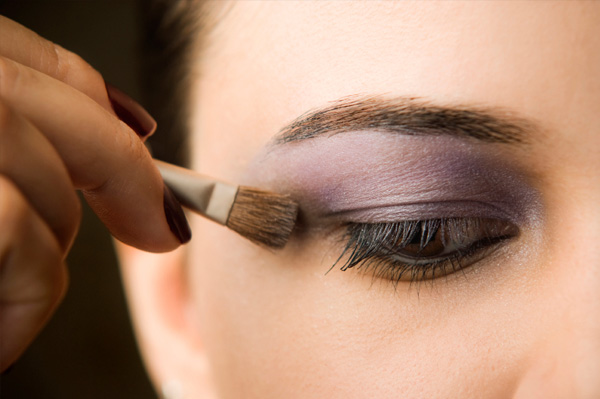 Woman applying purple eyeshadow