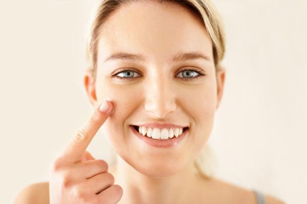 Woman applying tinted lotion