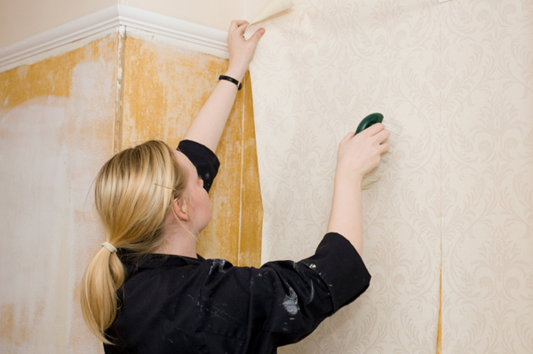 woman applying wallpaper