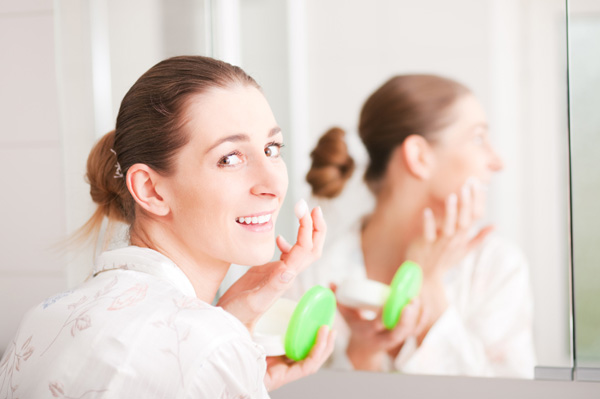 Woman applying face lotion
