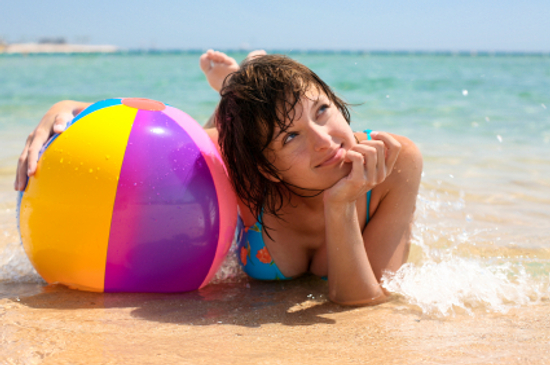 woman laying on beach with beach ball