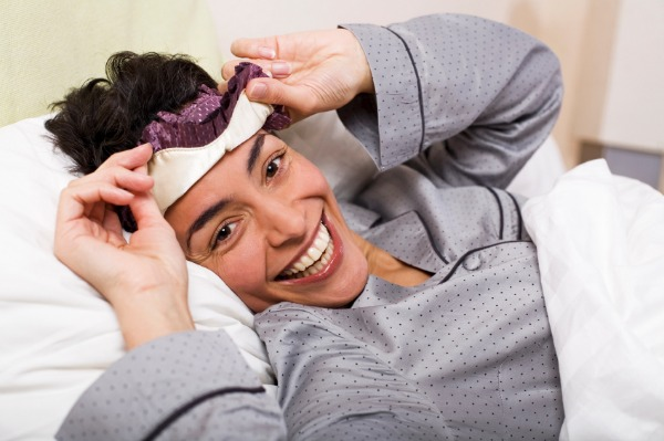 Woman lifting sleep mask