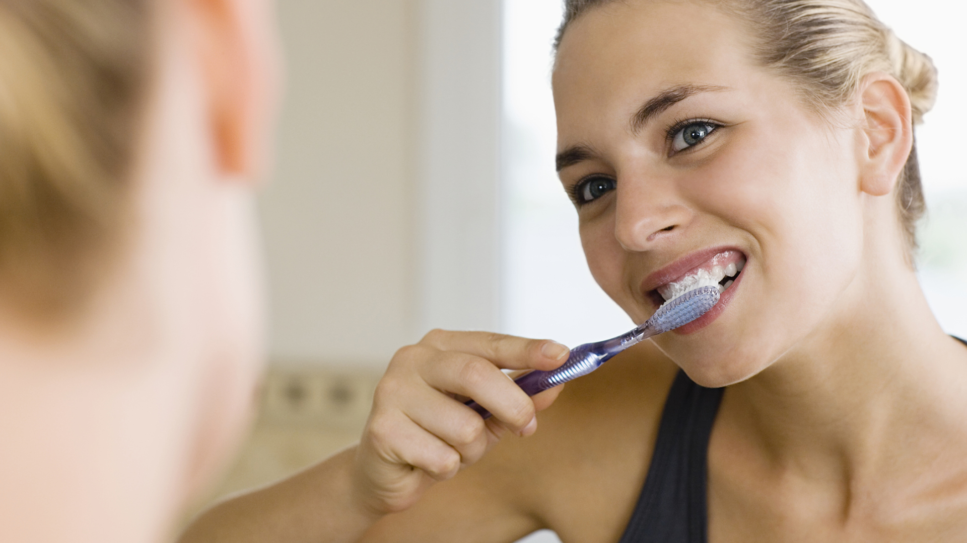 Woman brushing her teeth | Sheknows.com