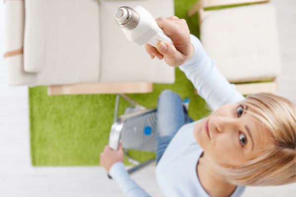 Woman changing CFL bulb