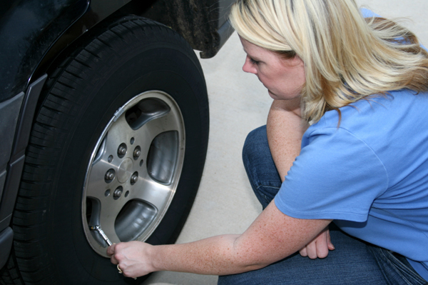 Woman checking air pressure in tires