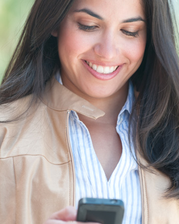 Woman smiling while checking smartphone