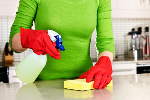 Woman cleaning kitchen with green cleaner