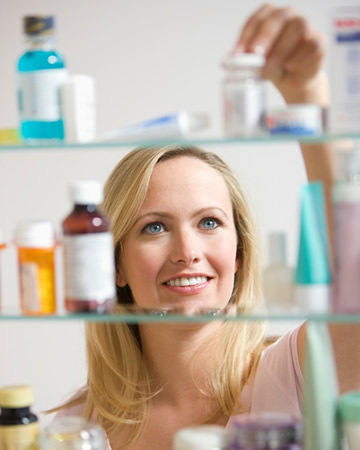 woman cleaning medicine cabinet