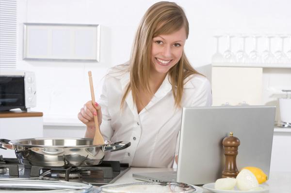 Woman cooking near laptop