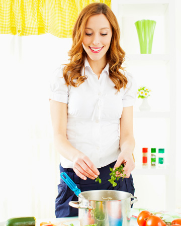 Woman cooking with herbs