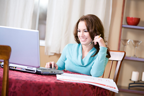 woman typing calendar into laptop