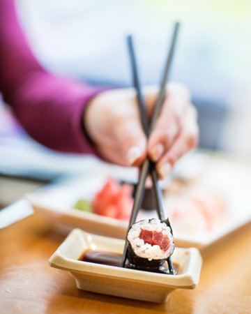 Woman dipping sushi in soy sauce