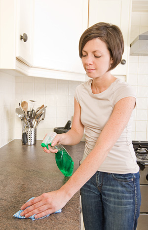 Woman disenfecting countertops