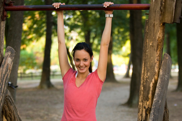 Woman doing chin-ups outdoors