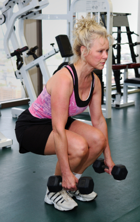Woman doing squats at gym