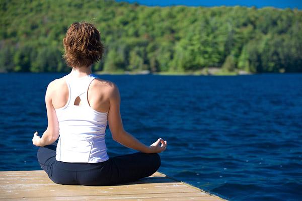 woman practicing yoga lakeside