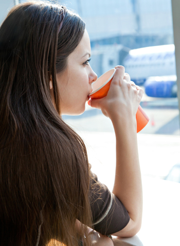Woman drinking coffee at airport
