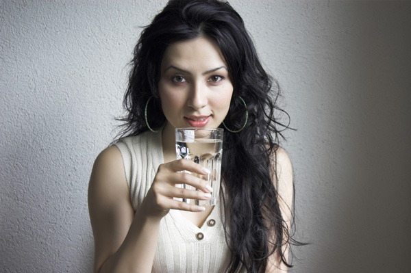 Woman with headache drinking water