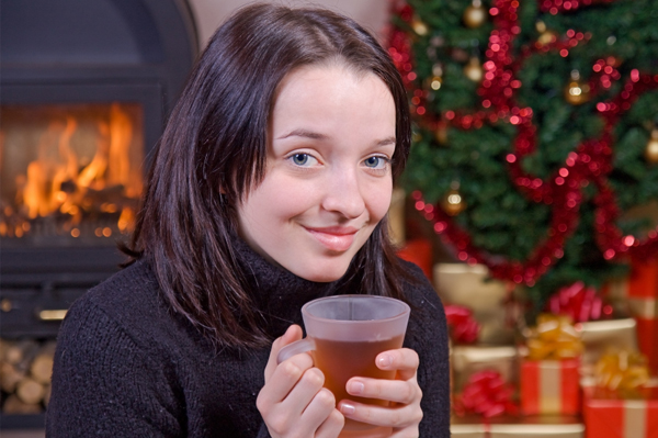 Woman drinking tea by fire