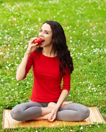 Woman eating apple after yoga