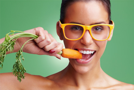 Woman eating carrot and wearing glasses