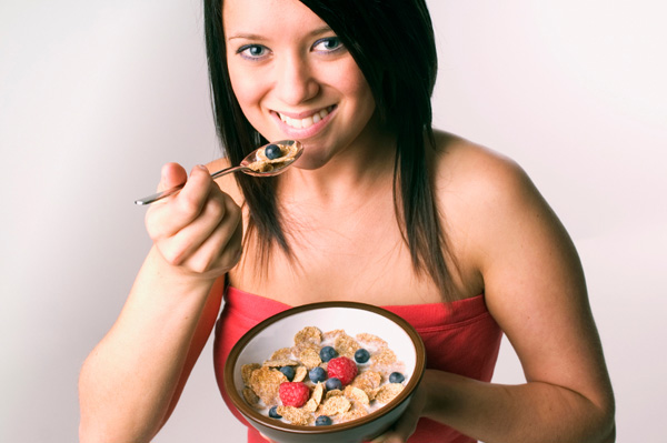 Woman eating cereal with fruit