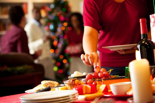Woman eating grapes at Holiday party