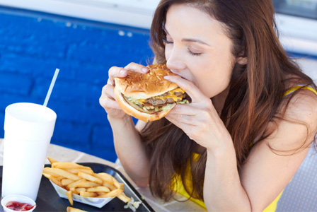 Woman eating greasy burger and fries
