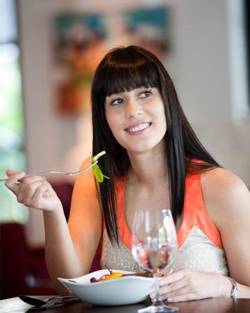 Woman eating salad at cafe