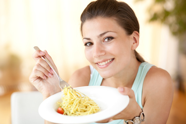 Woman eating pasta for breakfast