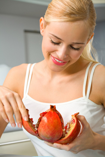 Woman eating pommegranate
