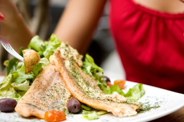 Woman eating salmon dinner