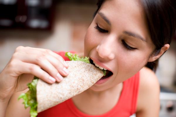 Woman eating whole wheat tortilla wrap