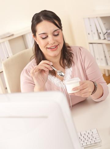 Woman eating yogurt at work