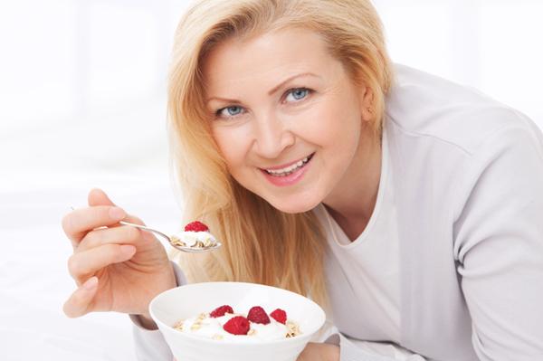 Woman eating yogurt and berries