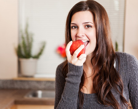 Woman eating apple in kitchen