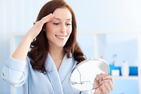 Woman shaping eyebrows