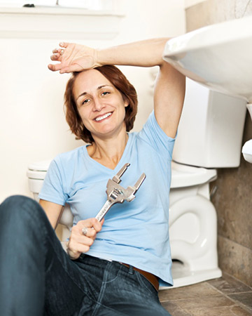 woman fixing leaky toilet